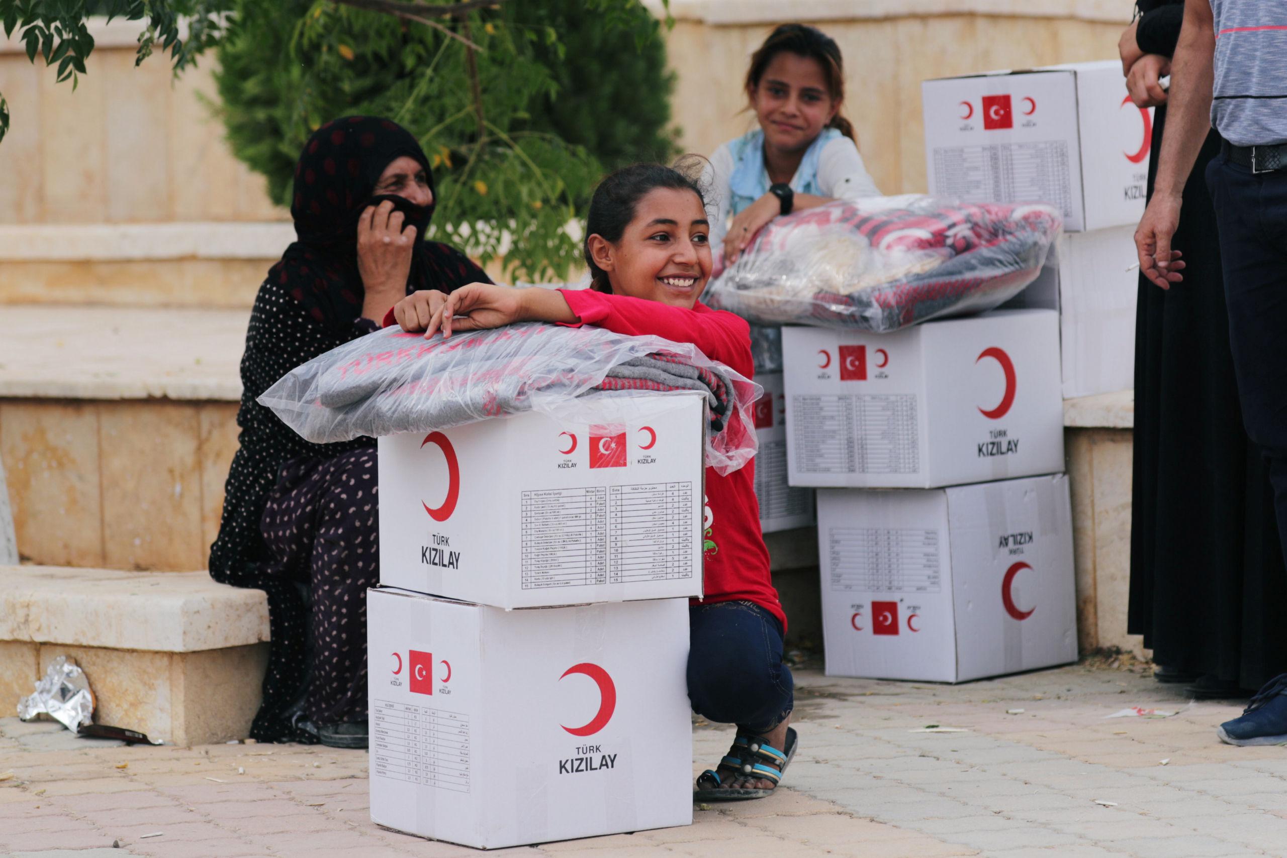 سيدة تتلقى مساعدات من الهلال الأحمر التركي في وقت سابق