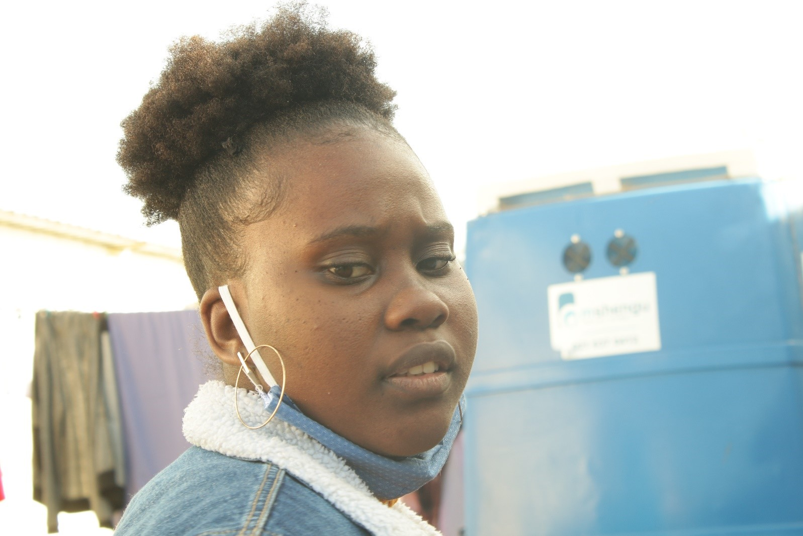Film director, Mona-Lisa Nsima, standing in front of a portable toilet in Khayelitsha [Gilroy Rinkwest]