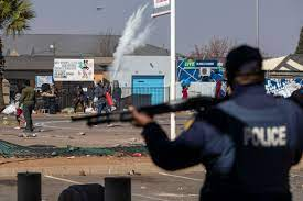 People throw stones at police in Katlehong east of Johannesburg [Themba Hadebe/AP]