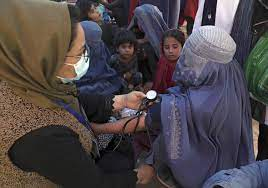 An internally displaced person from the northern provinces of Afghanistan has her blood pressure taken in Kabul, 2021.  [Rahmat Gul/AP]